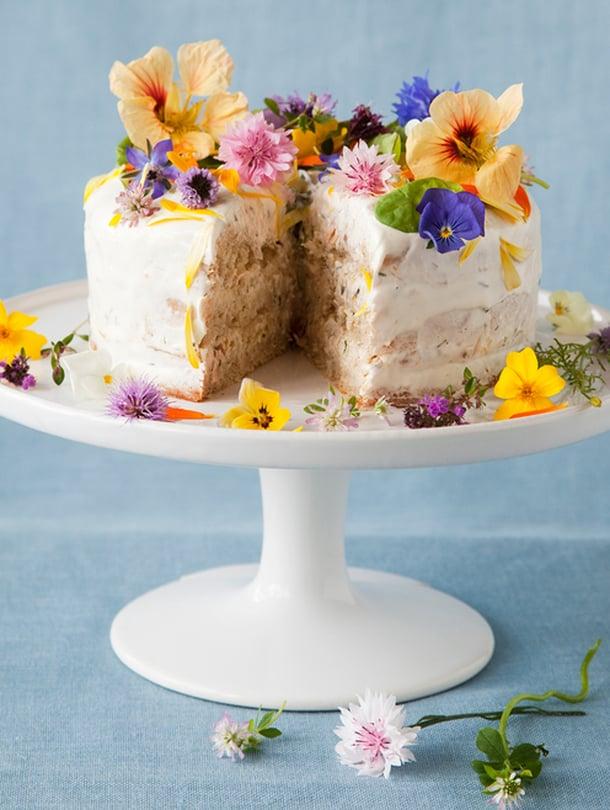 """Kukilla koristeltu pyöreä voileipäkakku ei häviä ulkonäössä makeille kakuille. Kuva: <span class=""""photographer"""">Arto Vuohelainen</span>"""